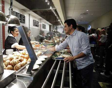 Diners get served at the food line at Cleburne Cafeteria during their soft opening, Tuesday, Nov. 14, 2017, in Houston. Cleburne Cafeteria, which was destroyed by fire in 2016, now features several upgrades including a patio, the ability to order wine and beer and some menu additions. ( Karen Warren / Houston Chronicle )