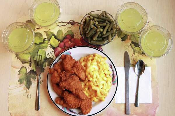 "This undated photo provided by the National Institutes of Health in June 2019 shows an ""ultra-processed"" lunch including brand name macaroni and cheese, chicken tenders, canned green beans and diet lemonade. Researchers found people ate an average of 500 extra calories a day when fed mostly processed foods, compared with when the same people were fed minimally processed foods. That's even though researchers tried to match the meals for nutrients like fat, fiber and sugar. (Paule Joseph, Shavonne Pocock/NIH via AP)"