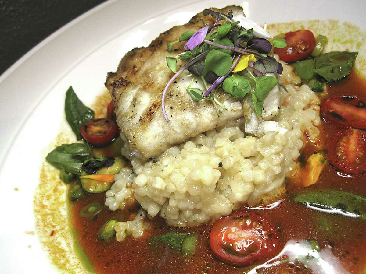 Pan-seared halibut gets a finish of couscous, charred tomato broth and fava beans at Mako's on the Creek in Cibolo.