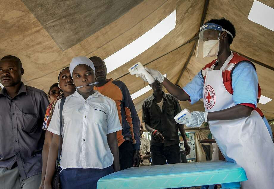 People arriving in Uganda from neighboring Congo have their temperature measured as part of screening for symptoms of possible Ebola infection at the Mpondwe border crossing. Photo: Ronald Kabuubi / Associated Press