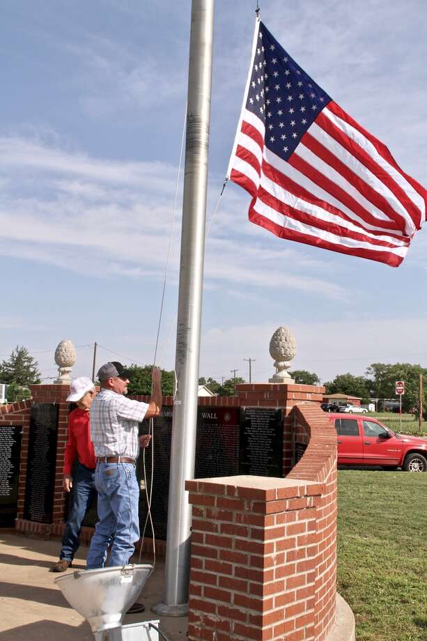 The new flag presented by Dick Shaver of the Woodman of the World is raised during a Flag Day ceremony on Friday morning at the Veterans Memorial Plaza in Hale Center. Photo: Don Brown/For The Herald