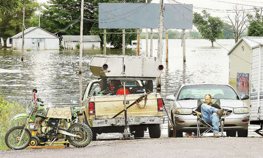 A man sits in a lawn chair in the middle of Red School Road in West Alton, Missouri, Friday at its intersection with U.S. 67, a flooded Red School Road behind him. The man apparently has been living in a small camper trailer parked next to him. Despite the dropping river levels, many people remain displaced from their homes in the West Alton area due to the flooding.