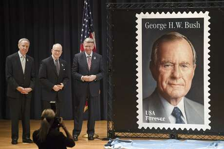David Jones, left, president and CEO of the George and Barbara Bush Foundation, is joined by Chase Untermeyer, former U.S. ambassador to Qatar and founding chairman of the Qatar-America Institute, and Robert Duncan, chairman, board of governors, United States Postal Service, as they stand beside the Forever Stamp featuring former President George H.W. Bush during a dedication ceremony Wednesday, June 12, 2019, at the Annenberg Presidential Conference Center in College Station, Texas.