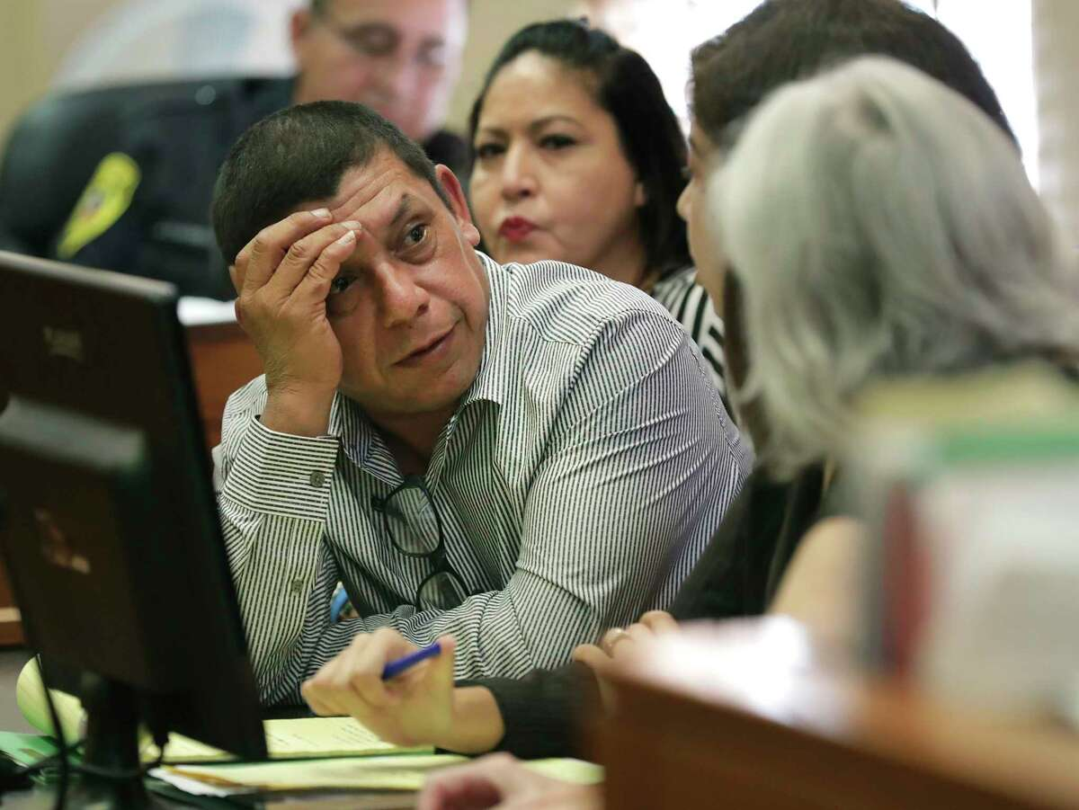 Fernando Yee, left, and his wife Maria Josephine Morales, center, grandparents of King Jay Davila, talks with lawyers in Children's Court before Judge Richard Garcia on Friday, June 14, 2019, in the Bexar County Courthouse.