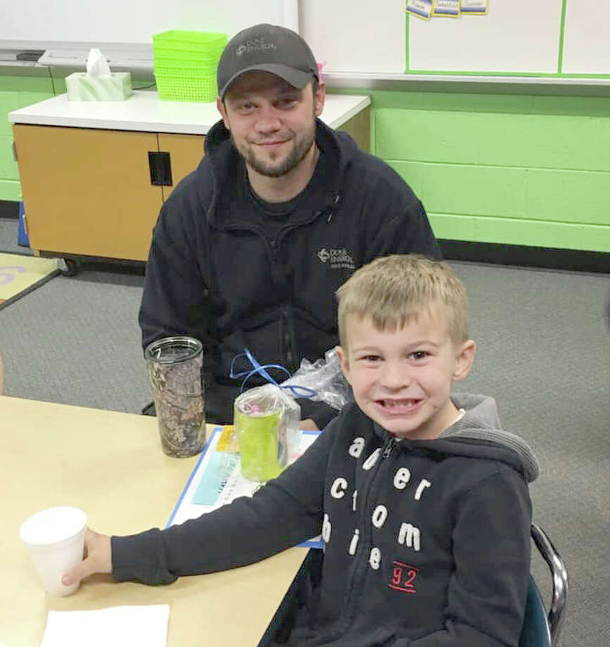 Dusty Maurer is pictured with his youngest son, Nate, at Bad Axe Elementary's Donuts with Dad event. (Robert Creenan/Huron Daily Tribune)