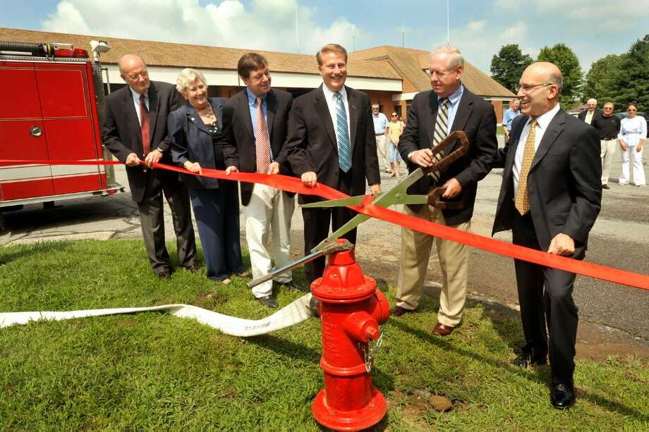Jerry Murphy, former Brookfield first selectman, cuts the ribbon celebrating a new water line at the Silvermine water line grand opening outside the Brookfield Firehouse on Thursday, July 29, 2010. Photo: Michael Duffy / The News-Times