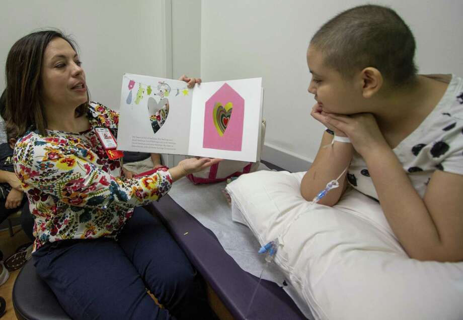 Pediatric Chaplain Jessica Shannon reads a book about sharing the heart's feelings to Gloria Palomino, 11, on Friday, June 14, 2019 at Texas Children's Hospital in The Woodlands. After each page of the book Shannon would ask Palomina to share similar feelings talked about on that page. Photo: Cody Bahn, Houston Chronicle / Staff Photographer / © 2019 Houston Chronicle