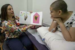 Pediatric Chaplain Jessica Shannon reads a book about sharing the heart's feelings to Gloria Palomino, 11, on Friday, June 14, 2019 at Texas Children's Hospital in The Woodlands. After each page of the book Shannon would ask Palomina to share similar feelings talked about on that page.