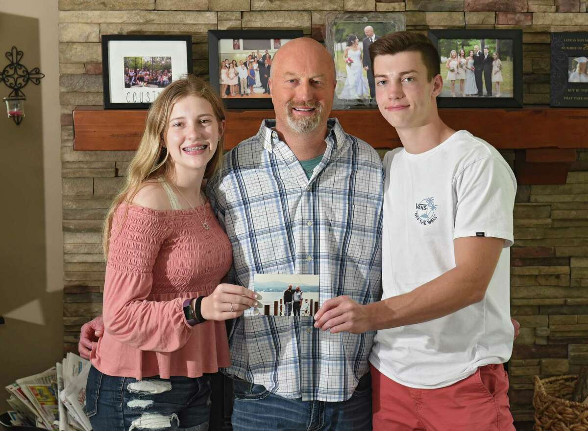 Jeff Malo stands in his home with his daughter Faith, 15, and his son Bailey, 17, on Friday, June 14, 2019 in Loudonville, N.Y. Jeff's father James Malo, Sr. donated a kidney to him back in 1990. The photo of Jeff and his father they are holding was taken a couple of years after the transplant. (Lori Van Buren/Times Union)