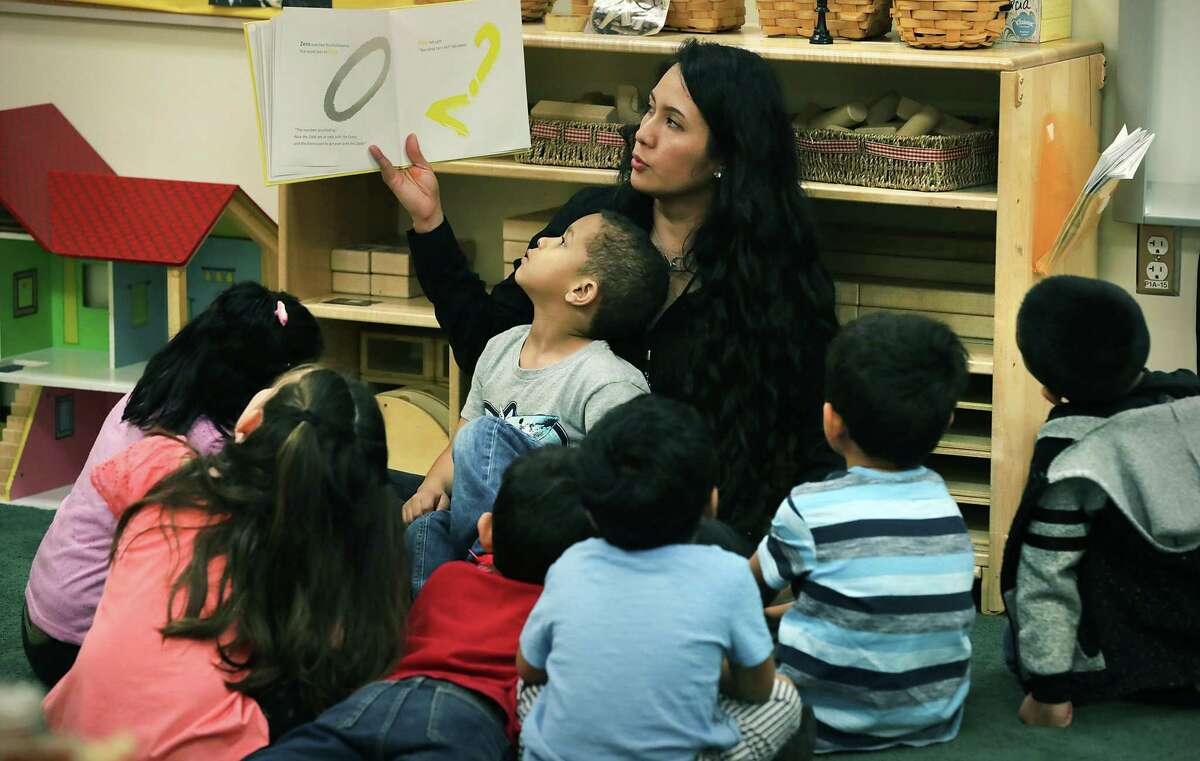 Teacher Alejandra Sanchez reads a book to her students with Trevor Steen sitting in her lap at the Pre-K 4 SA North Center last March.