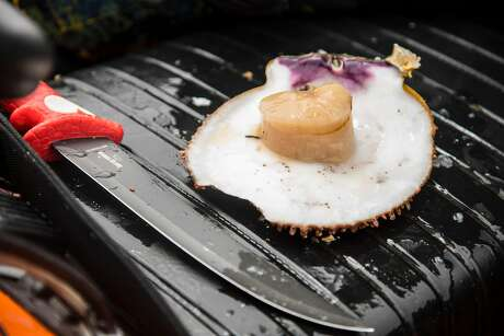 Greg Fonts prepares a raw scallop to eat on the seat of his boat while spearfishes and free diving for shell fish off the north coast of California near Fort Bragg on Sunday, May 12, 2019. Photo: Brian Feulner / Special To The Chronicle