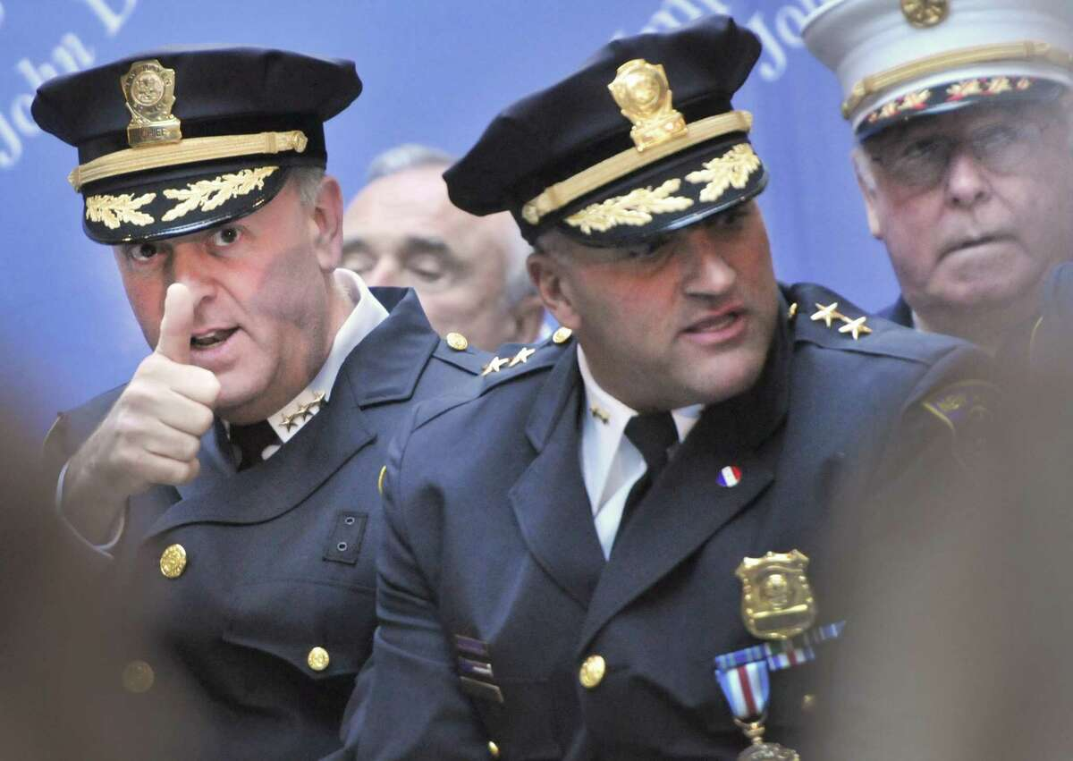 Then new Police Chief Dean M. Esserman, left, gives a thumbs up to a member of the audience before his swearing in ceremony at New Haven City Hall in Nov. 18, 2011. Sitting with Esserman is then Assistant Police Chief John Velleca, center, and then New Haven Fire Chief Michael Grant, right.
