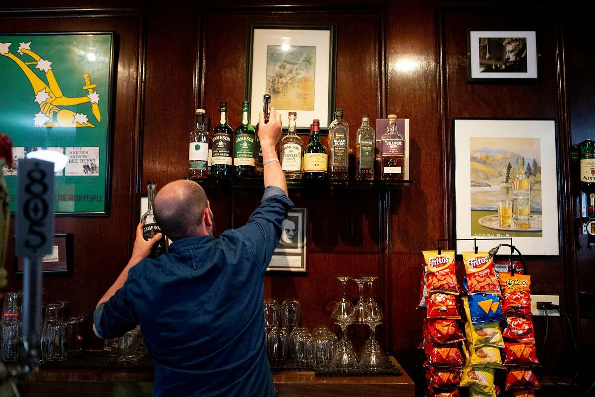 Eoin Malone Hobden grabs a bottle of Irish Whiskey at the Plough and the Stars Wednesday, June 5, 2019, in San Francisco, Calif. The Irish pub is located at 116 Clement St.