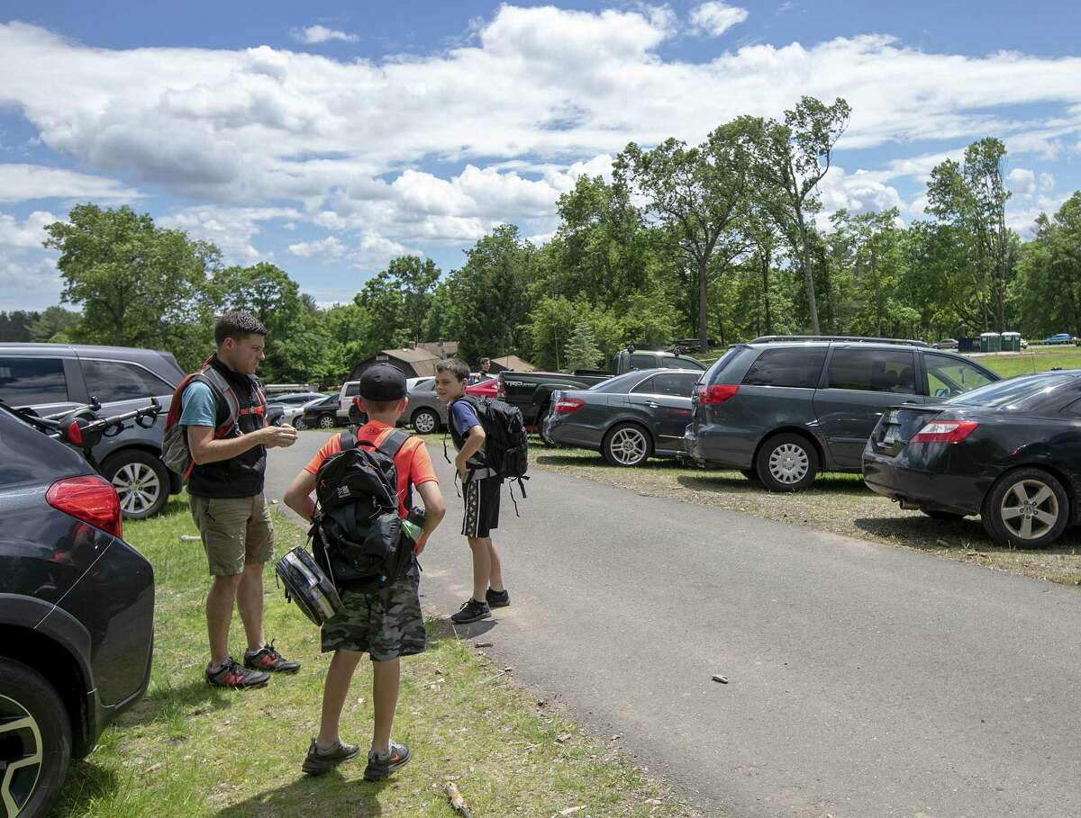 Brendan Holt, left, and son Ronan, 10, right, along with friend, Max Pugliese, 10, second from left, get ready to hike the trails at Sleeping Giant State Park in Hamden, Conn., Friday, June 14, 2019. The park has opened a year after a tornado ravaged the landscape. (Dave Zajac/Record-Journal via AP)