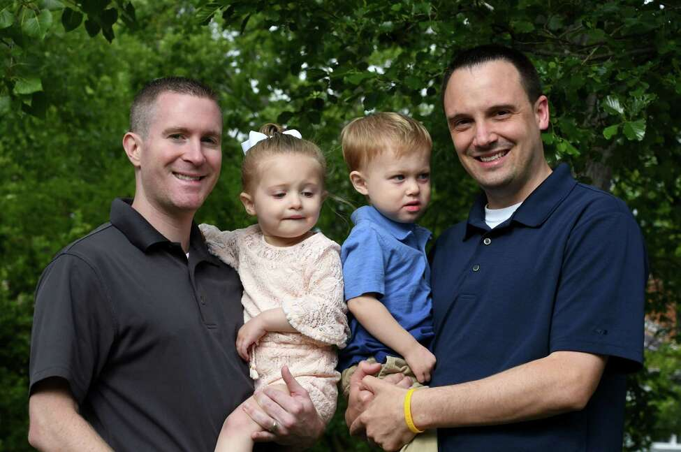 Kevin Karr-McGraw, left, and Sean McGraw, right, with their daughter and son on Friday, June 14, 2019, in Albany, N.Y. The married couple had their children through surrogacy. The process cost over $100,000 and involved multiple trips to California and Texas, where their twins were eventually born in 2017. (Will Waldron/Times Union)