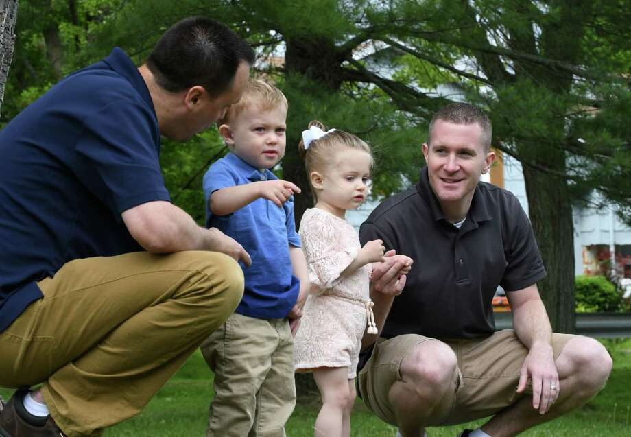 Sean McGraw, left, and Kevin Karr-McGraw, right, with their son and daughter on Friday, June 14, 2019, in Albany, N.Y. The married couple had their children through surrogacy. The process cost over $100,000 and involved multiple trips to California and Texas, where their twins were eventually born in 2017. (Will Waldron/Times Union) Photo: Will Waldron, Albany Times Union / 40047237A