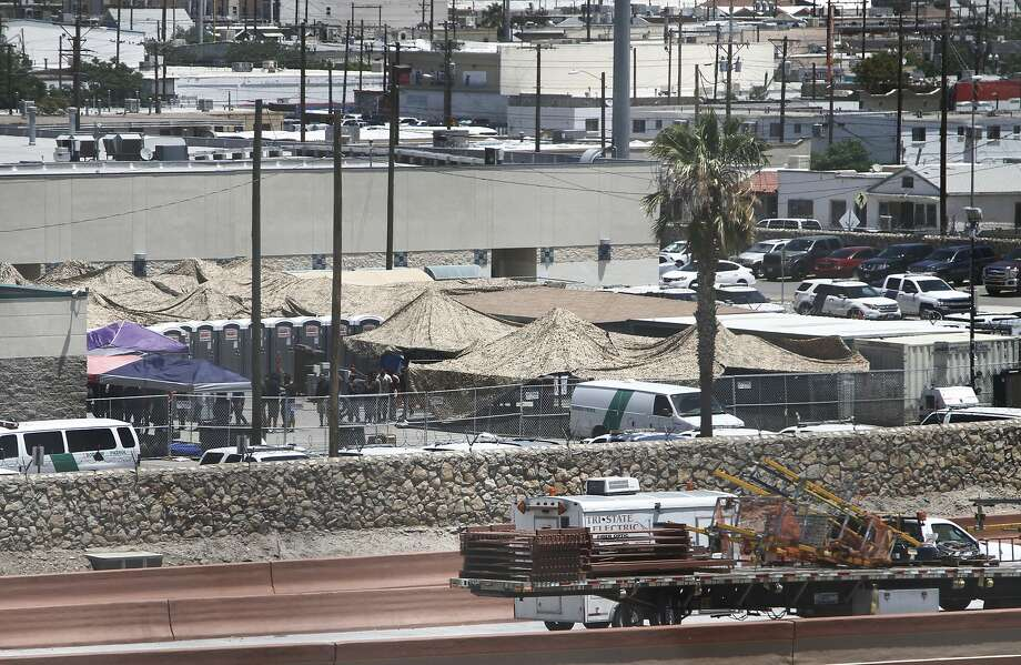 Migrants are held Wednesday within a fenced-off area inside a temporary outdoor encampment where they're waiting to be processed in El Paso, Texas. Photo: Cedar Attanasio / Associated Press