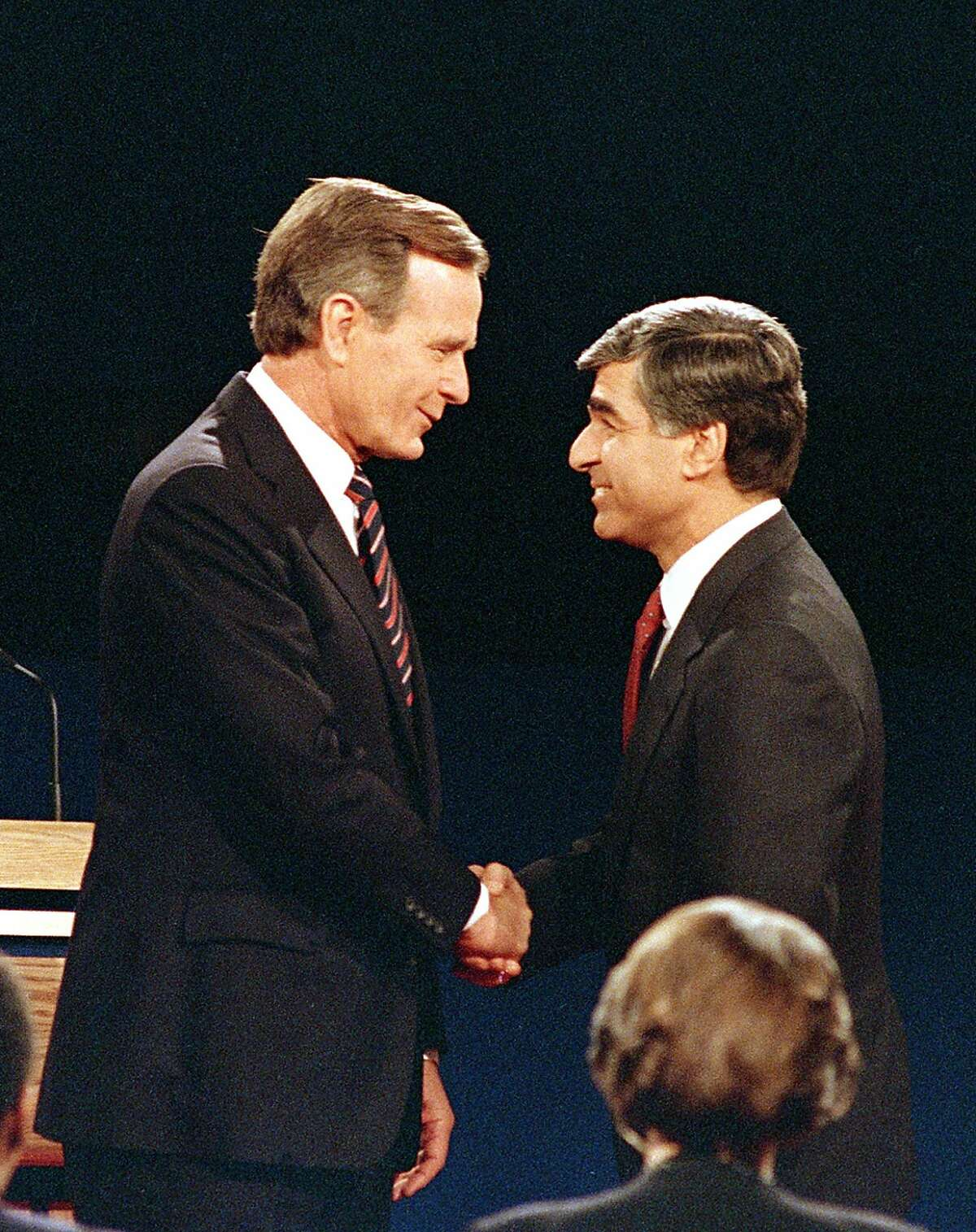 FILE - In this Oct. 13, 1988 file photo, Democratic presidential candidate and Massachusetts Gov. Michael Dukakis shakes hands with Vice President and Republican presidential candidate George Bush, left, prior to their second and final presidential debate on UCLA's campus in Los Angeles, Calif. During the debate Dukakis was asked whether he'd favor the death penalty if his wife, Kitty, were raped and murdered. His emotionally detached a classic case of being too cool under fire.