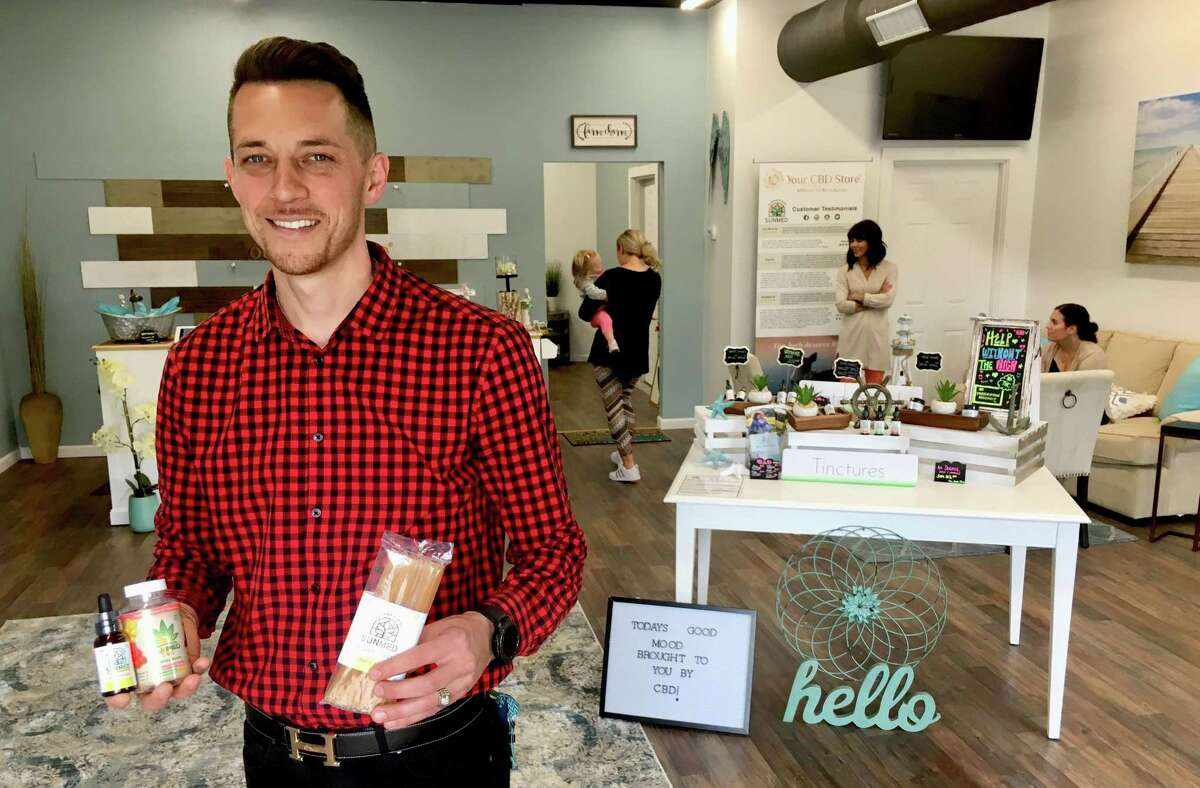 Clayton Percy, chief operating officer and general manager of the Your CBD Store location in Milford, in the store with products. The store is one of nearly 400 franchised or affiliated with the Florida company Sunflora.