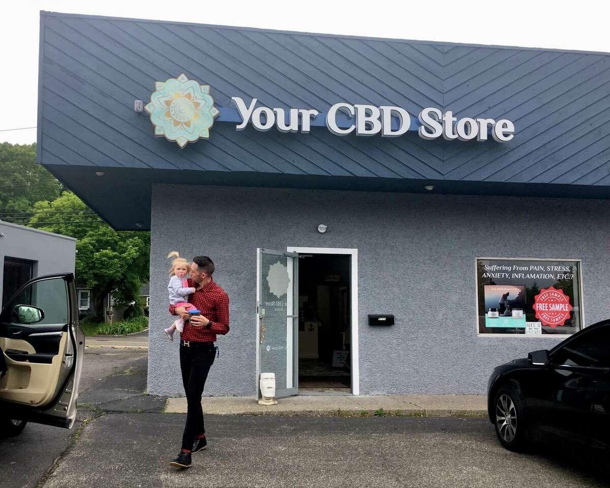 Clayton Percy, co-owner and general manager of the Your CBD Store location in Milford, in the store with products. The store is one of nearly 400 franchised or affiliated with the Florida company Sunflora.