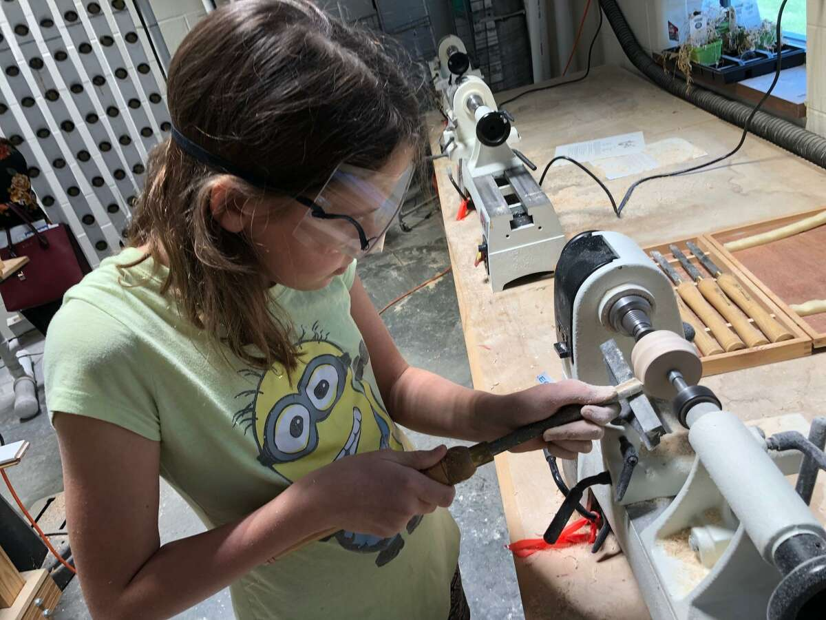 Brenna Arnold, 11, uses a gouge to carve a piece of wood on a lathe duringKaty Independent School District's fifth annual STEM Summer Camp.