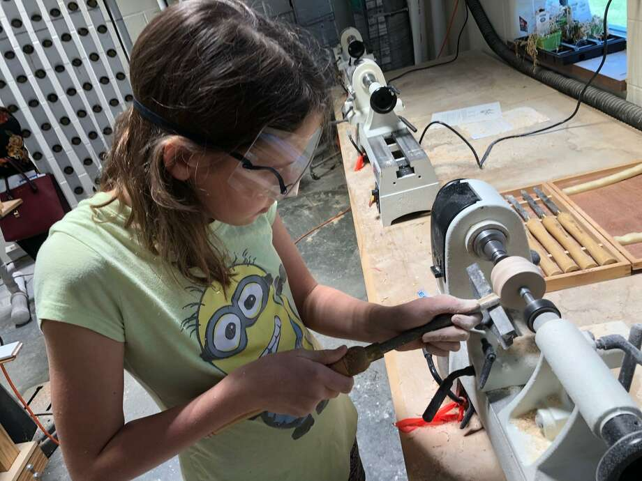 Brenna Arnold, 11, uses a gouge to carve a piece of wood on a lathe during Katy Independent School District's fifth annual STEM Summer Camp. Photo: Mike Glenn / Staff Photo
