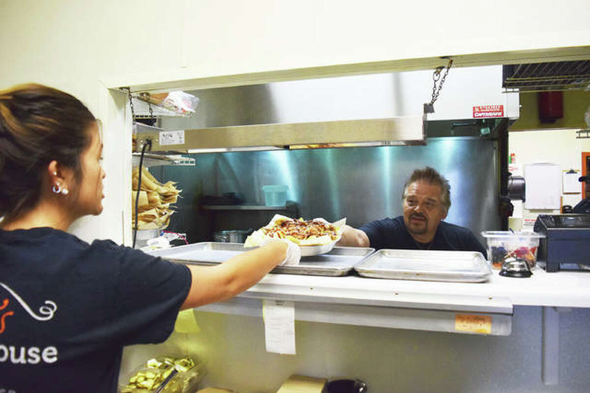 Doc Richardson, owner of Doc's Smokehouse, hands off a plate of food to Sabrina Fosse, a crew member at Doc's