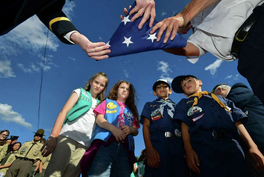 Scouts including Genevive Freedman, 9, Isabella Frey, 8, Nasif Kahn, 7, and Adam Asuncion, 7, watch Army National Guard Captian Brian Rooney and Deputy Chief Edward Prescott properly fold a flag during a ceremony on Flag Day to respectfully retire worn American flags that have been proudly flown over Norwalk, on Friday, at the Norwalk Fire Department maintenance garage in Norwalk. The ceremony, organized by The American Legion Frank C. Godfrey Post 12, the Norwalk Fire Department and Scouts BSA Troop 19, invited all community organizations, interested citizens and Scout units to participate. Photo: Erik Trautmann / Hearst Connecticut Media / Norwalk Hour