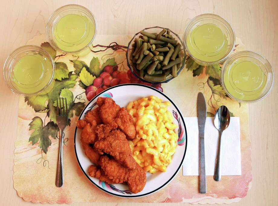 "This undated photo provided by the National Institutes of Health in June 2019 shows an ""ultra-processed"" lunch including brand name macaroni and cheese, chicken tenders, canned green beans and diet lemonade. Researchers found people ate an average of 500 extra calories a day when fed mostly processed foods, compared with when the same people were fed minimally processed foods. That?s even though researchers tried to match the meals for nutrients like fat, fiber and sugar. (Paule Joseph, Shavonne Pocock/NIH via AP) Photo: Paule Joseph Shavonne Pocock / National Institutes of Health"