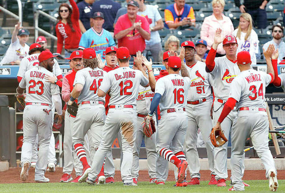 The Cardinals celebrate on the field after the they defeated the New York Mets 5-4 in 10 innings Friday in New York in a continuation of a game that had been suspended Thursday because of rain. Paul DeJong (12) drove in Yairo Munoz, right, with the go-ahead run. The Cardinals also won the regularly scheduled game Friday night 9-5.