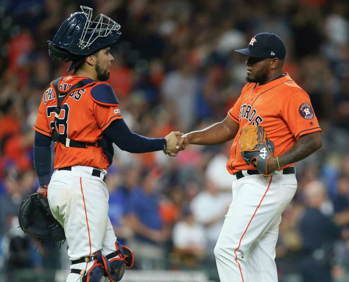 Houston Astros catcher Robinson Chirinos (28) shakes hands with relief pitcher Rogelio Armenteros (61) after a successful save of the MLB game against the Toronto Blue Jays at Minute Maid Park on Friday, June 14, 2019, in Houston. The Houston Astros defeated the Toronto Blue Jays 15-2.