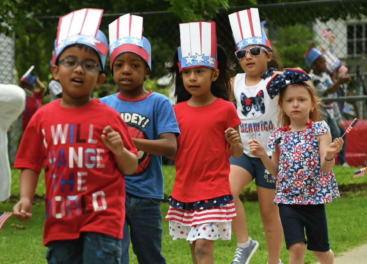 School 14 students parade into school during their annual Red, White and Blue Day celebration to commemorate Flag Day on Friday morning, June 14, 2019, in Troy, N.Y. Flag Day honors the adoption of the U.S. flag on June 14, 1777. (Will Waldron/Times Union)