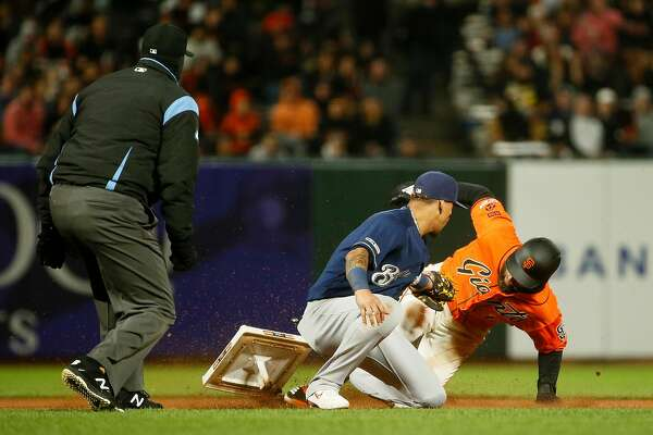 San Francisco Giants center fielder Kevin Pillar (1) is safe at second base after he slided and dislodged the base in the seventh inning during an MLB game Milwaukee Brewers shortstop Orlando Arcia (3) at Oracle Park on Friday, June 14, 2019, in San Francisco, Calif.