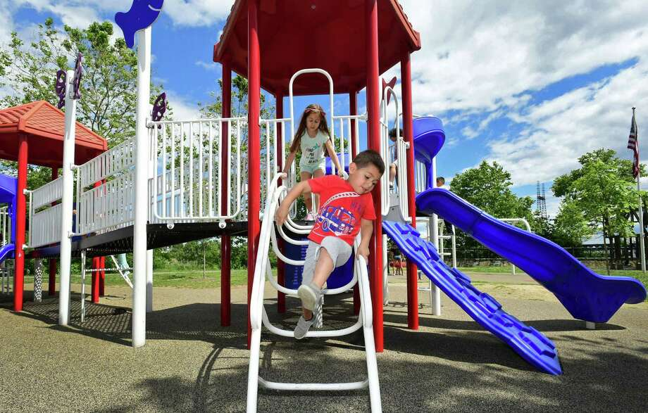 Children including Valeria and Alfonso Ochoa, 7 and 4, play at the Sandy Ground, Where Angels Play project playground dedicated to Allsion Wyatt the Friday, June 14, 2019, at Osyter Shell Park in Norwalk, Conn. As a part of the Walk Bridge Program, the state DOT will be doing remediation along the river at Oyster Shell Park. However, in order to do so, the playground will need to be closed for about 2 months in the spring of 2021. Please get a few photos of the playground and overlooking the river from the park. Photo: Erik Trautmann / Hearst Connecticut Media / Norwalk Hour