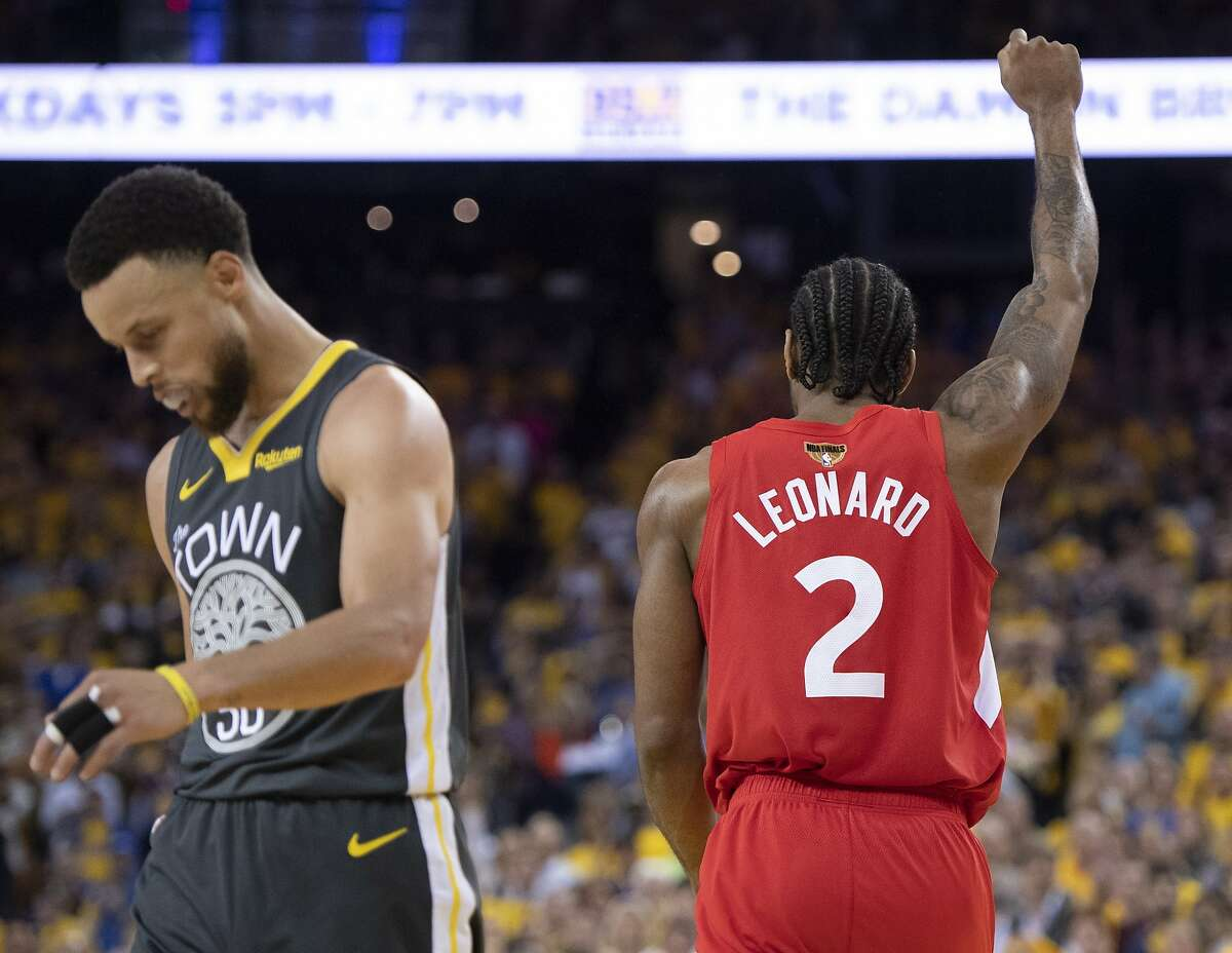 Toronto Raptors' Kawhi Leonard raises his fist following a basket as Golden State Warriors' Steph Curry walks away during the second half of Game 6 of basketball's NBA Finals, Thursday, June 13, 2019, in Oakland, Calif.