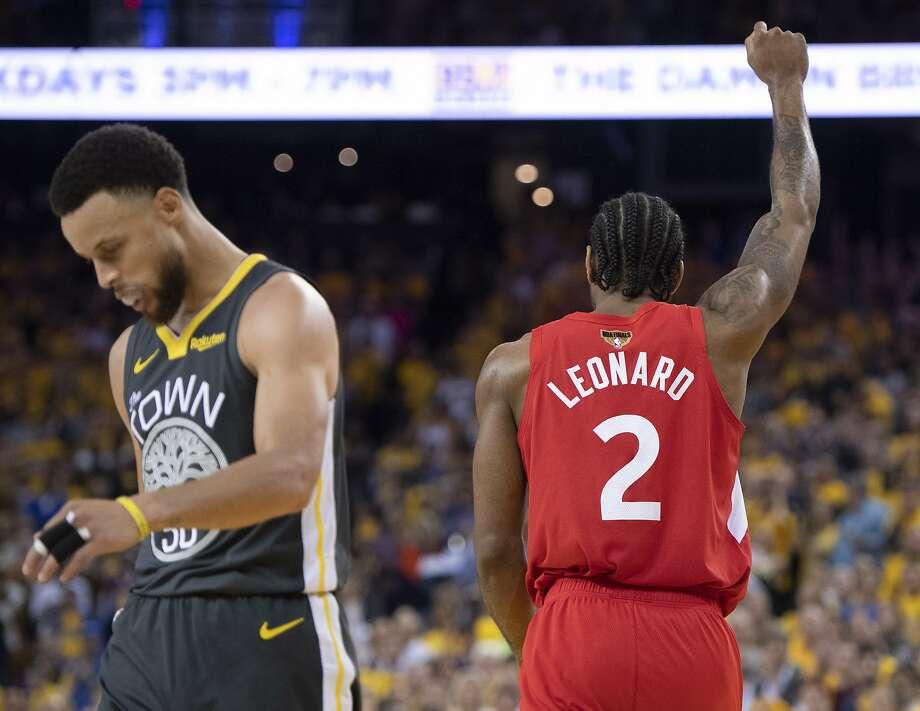 Toronto Raptors' Kawhi Leonard raises his fist following a basket as Golden State Warriors' Steph Curry walks away during the second half of Game 6 of basketball's NBA Finals, Thursday, June 13, 2019, in Oakland, Calif. Photo: Frank Gunn / Associated Press