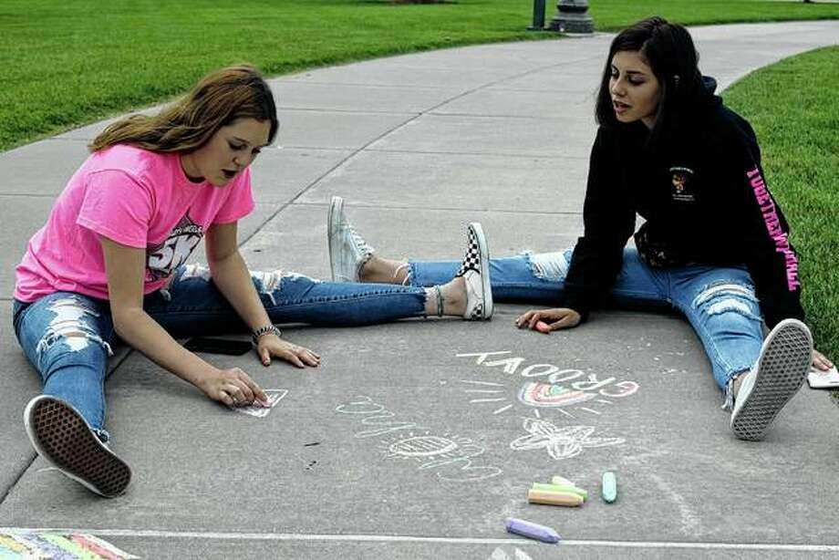 Brooklyn Clayton (left) and Alandra Antle draw with chalk before the performance of Dirty Revival Friday on the downtown square. Photo: Samantha McDaniel-Ogletree | Journal-Courier