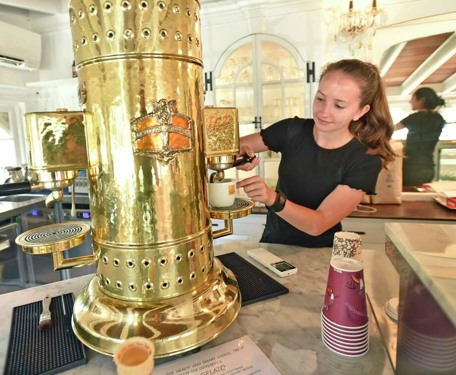 """Old Saybrook,  Connecticut - Saturday,  June 15, 2019:   Employee Julia Sultiani makes an Americano coffee with a  an italian """"handmade"""" espresso machine made of copper, brass and chrome, reportedly the only espresso machine of its kind in the U.S.A., at the Caffe Marche in Old Saybrook, located in the historic James Pharmacy Bed & Breakfast and Gelateria, whose baristas offer authentic Italian coffee, espressos, capuccinos, lattes, gourmet Connecticut coffees and cold brews,  teas, local pastry and other repasts. Gelato is made fresh daily with natural italian products and fresh Farmer's Cow milk from Connecticut. Juices, smoothies, protein shakes, milk shakes and floats are also something to experience. Photo: Peter Hvizdak, Hearst Connecticut Media / New Haven Register"""