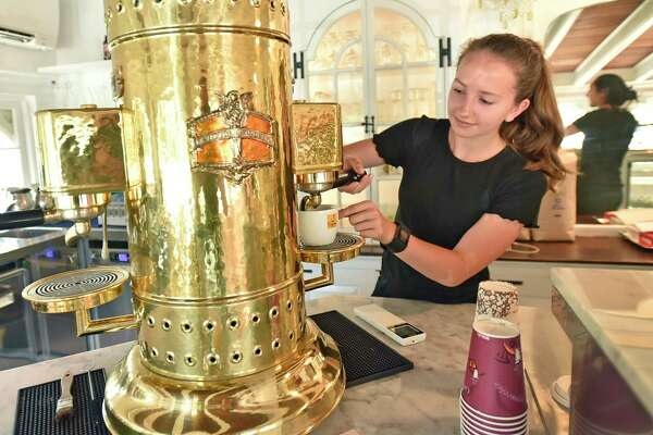 """Old Saybrook, Connecticut - Saturday, June 15, 2019: Employee Julia Sultiani makes an Americano coffee with a an italian """"handmade"""" espresso machine made of copper, brass and chrome, reportedly the only espresso machine of its kind in the U.S.A., at the Caffe Marche in Old Saybrook, located in the historic James Pharmacy Bed & Breakfast and Gelateria, whose baristas offer authentic Italian coffee, espressos, capuccinos, lattes, gourmet Connecticut coffees and cold brews, teas, local pastry and other repasts. Gelato is made fresh daily with natural italian products and fresh Farmer's Cow milk from Connecticut. Juices, smoothies, protein shakes, milk shakes and floats are also something to experience."""