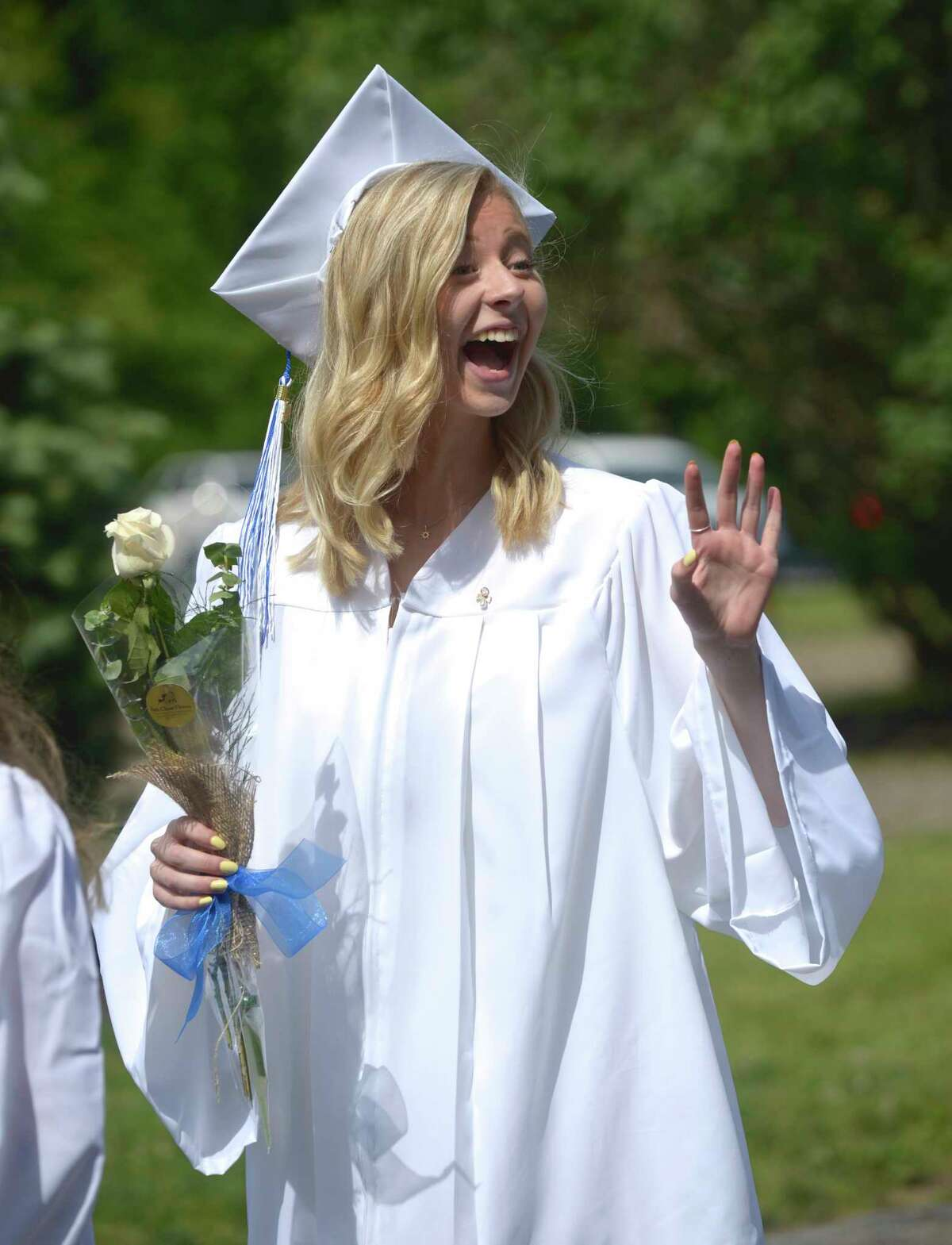Lana Marie DelVecchio, of Bridgewater, waves during the procession for the Shepaug Valley High School Class of 2019 Commencement, Saturday morning, June 15, 2019, on the Bryan Memorial Town Hall lawn, Washington, Conn.