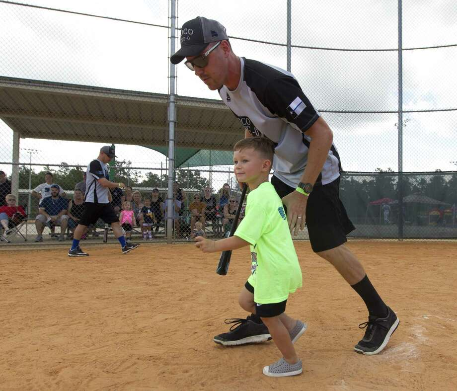 Patrick Reed runs with his son, Jackson, after a hit during the inaugural Americans Stand United First Responder Softball Tournament at Carl Barton, Jr. Park, Saturday, June 15, 2019, in Conroe. Each child was pair with a firefighter or police officer as a coach for the game. The inaugural tournament brought together community members with 150 first responders from Montgomery and Harris County. Photo: Jason Fochtman, Houston Chronicle / Staff Photographer / Houston Chronicle