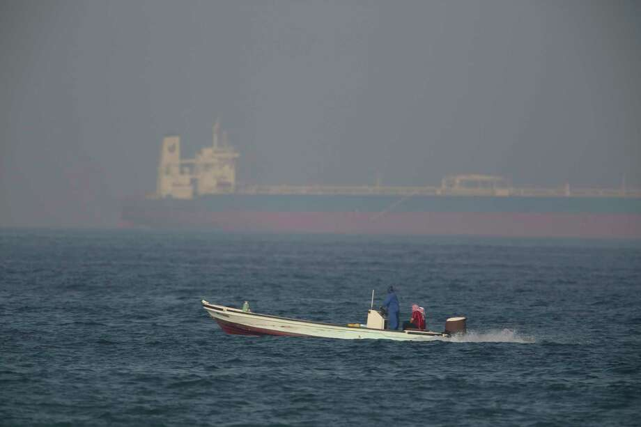 A fishing boat speeds past an oil tanker in the distance in Fujairah, United Arab Emirates, Saturday, June 15, 2019.  Photo: Jon Gambrell / Copyright 2019 The Associated Press. All rights reserved.