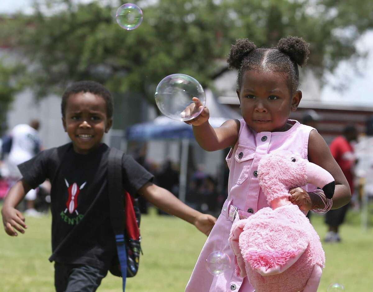 Aza Ashé, 3, reaches to poke a bubble while playing with Kamau Rikondja, 4, and Osahar Rikonja, not in photograph, at the 147th annual Juneteenth Celebration at Emancipation Park on Saturday, June 15, 2019, in Houston.
