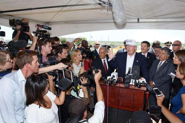 ARCHIVO- El candidato presidencial del partido Republicano, Donald Trump, en el podium, es rodeado por funcionarios de la ciudad y representantes de los medios de comunicación durante una conferencia de prensa llevada a cabo el 23 de julio de 2015 en el Puente Mundial de Comercio.