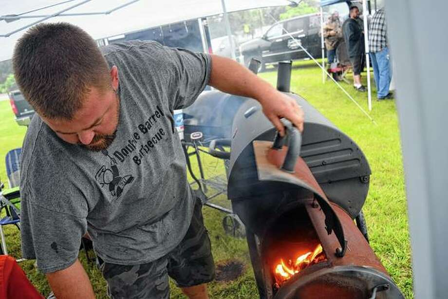 Clint Rahe of Double Barrel Barbecue checks the fire Saturday while cooking food at the Morgan County Fairgrounds despite the weather, which caused Jacksonville Kiwanis Club to postpone the Jacksonville BBQ Braggin' Rights competition.