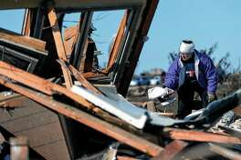Candy Trudell searches for her belongings in the rubble after a tornado struck the town of Rochelle in Illinois in April 2015.