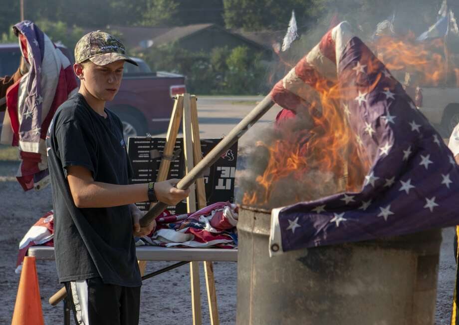 Jacob VanJura, 15, burns a flag for its retirement during a Flag Day ceremony Friday, June 14, 2019 at VFW Post 4709 in Conroe. Photo: Cody Bahn/Staff Photographer