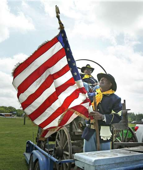 Jerry Cheaton folds up the flag after he and other Bexar County Buffalo Soldiers marched in a parade to Comanche Park No. 2.
