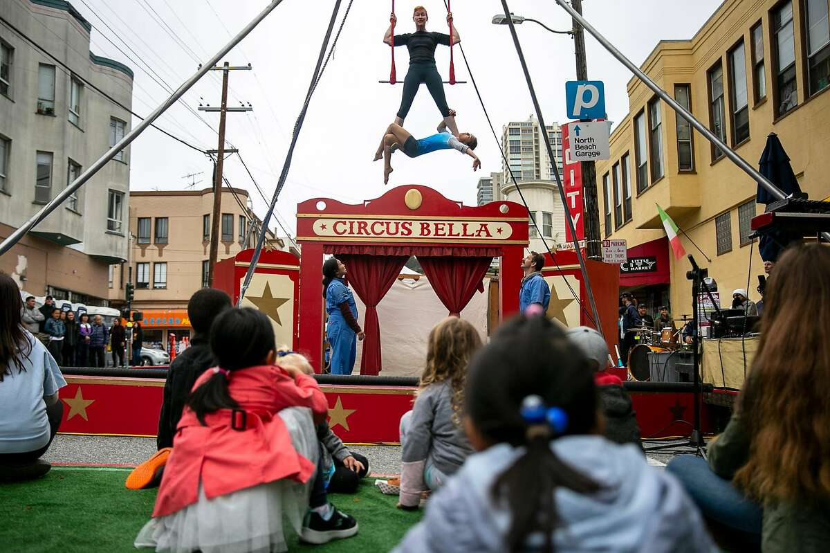 During a warm up for a performance of Circus Bella, Abigail Mann suspends Guilia Gentile, 10, mid air on the trapeze at the 65th annual North Beach Festival on Sunday, June 16, 2019, in San Fransisco, Calif.