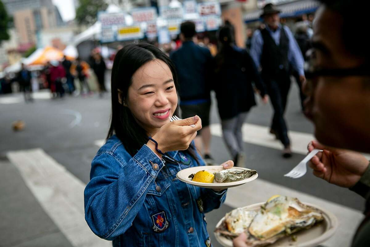 Kelly Zhong of San Fransisco smiles at Chris An as they eat oysters at the 65th annual North Beach Festival on Sunday, June 16, 2019, in San Fransisco, Calif.